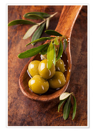 Plakat Spoon with green olives on a wooden table